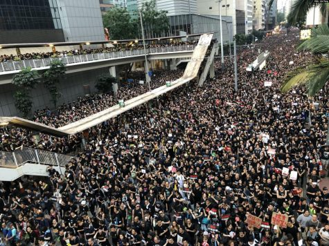Protesters in black in Hong Kong, large amount of people forces police to open up more roads. Taken from Wikimedia Commons